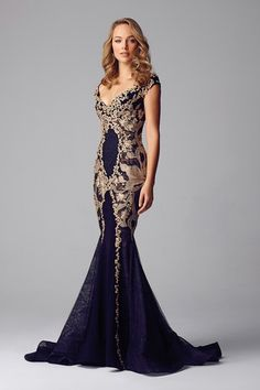 A beautifully elegant evening gown from Alberto Makali. Gold pattern is a perfect and eye-catching design against a dark blue dress. Fall 2015 Collection.