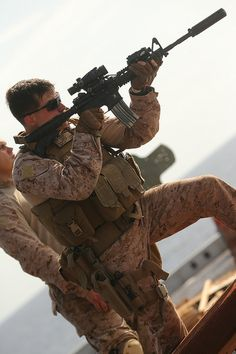 Marines with the Force Reconnaissance detachment, Marine Expeditionary Unit, fire their carbines from behind cover during a close-quarters tactics and movement.