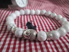 Beautiful White Howlite Natural Stone and Silver Buddha Bracelet. Howlite is said to help to reduce anxiety, tensions and stress. Howlite can be used to facilitate awareness, encourage emotional expression and assist in the elimination of pain, stress.