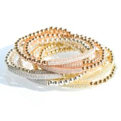 A fun and fresh new take on style, this bracelet add the perfect accent to your day and evening wear. Silver beads create the unique stretch bracelet with a brilliant pave cubic zirconia bar shining boldly in the center. The beads are hand-strung and knotted securely on a elastic cord for a slip on style.