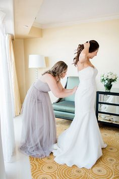 Hometown Boston Wedding, Bride Getting Ready in Lace Trumpet Gown  | Brides.com