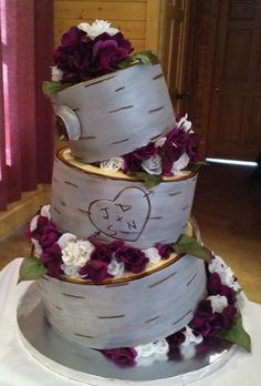 Triple tier topsy turvy silver birch tree themed cake adorned with burgundy and white flowers and decorative initial etching on the center tier, designed by Sweet Pea Cake Company of Colorado Springs.