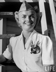 Anne Armstrong McClellan, pilot trainee in Women's Flying Training Detachment, sporting an official dress uniform of white blouse, tan slacks and overseas cap & a Fifinella mascot pin designed for the girl pilots by Walt Disney - Avenger Field, Sweetwater, Texas - Photographer: Peter Stackpole - July 1943.