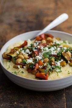 A hearty vegetarian dish that starts with a base of creamy polenta and is topped with chickpeas, feta, and flavorful curry grilled vegetables.