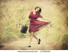Redhead girl with suitcase at tree's alley. by Masson, via Shutterstock