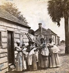 Five African–American women pose for a portrait with their babies beside slave quarters on St. Helena Island, S.C., in 1866.