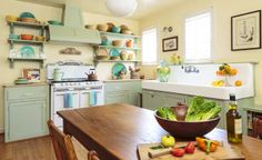 Lucky shopping finds—a vintage stove and salvaged apron sink—set the tone in this revitalized 1930s kitchen. Other charming choices, such as the sage green Shaker-style cabinets and vintage-inspired fixtures, add to the room's classic beauty. Open shelves turn everyday dishes into an artful display.