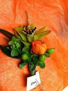 Grooms boutonniere by Weddings by Jennifer, via Flickr Mini green cymbidium orchid, orange ranunculus and green hypericum berries.