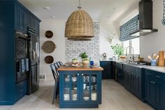 To add distinctive style and personality, the kitchen at HGTV Urban Oasis 2017 focuses on eye-catching textures with a mix of historic windows, whitewashed brick and navy blue cabinets.