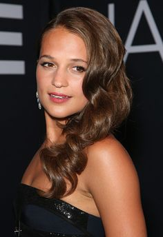 To nail Alicia Vikander's beauty look, side-part your locks then divide into three sections, twisting each in a curling wand or tongs to create big, bouncy curls. Shake out the segments and hairspray into place, keeping it all over one shoulder if your hair is long enough. Pink lips and a slathering of mascara, and you're good to go