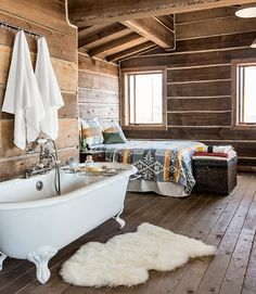 """The cabin is furnished with everything that's necessary—and nothing more. No fancy appliances grace the kitchen, but there is a vintage claw-foot tub in the bedroom. """"The house has a certain simplicity to it that's beautiful,"""" Bueno says. In this photo: The sheepskin is from Room & Board; a Pendleton blanket and shams dress the bed. Plus: 100 bedroom design ideas you'll love »   - CountryLiving.com"""