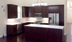 beautiful cherry cabinets in remodeled kitchen with white tile backsplash and white quartz countertop, white