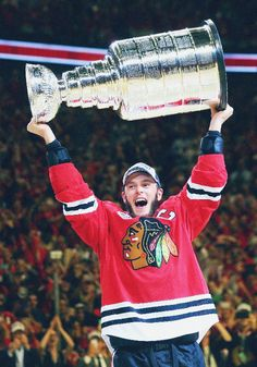 """Jonathan Toews of the Chicago Blackhawks celebrates by hoisting the Stanley Cup."""