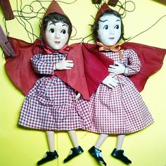 #818_Little_Red_Riding_Hood (ca. 1958). A new Red (left) arrived at my house today. I thought this marionette would be a duplicate of one I already had (right). I bought it because it was such a good price. But when I saw them together, I found that not only do they have different coloring but the costumes are quite different. The new one has a bigger hood/cape, but more interesting too me is that she has a real gingham fabric dress. The other is a gingham print.