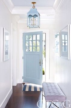 A coastal blue door invites guests into a clean, classic foyer. #coastalcottageexterior #beachcottagesinterior
