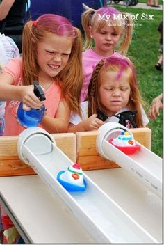 Aus halben Plastikrohren eine Bahn basteln. Nun müssen die Kids die Boote mithilfe eines Pflanzensprühers schnell ins Ziel bringen.