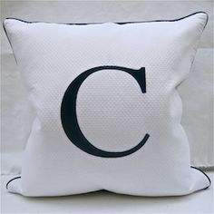This pique pillow comes in navy, orange, and lime green lettering.