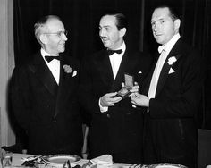 Walt Disney at an awards ceremony posing with a medal. Nathan Levinson is pictured left and E. A. Williford is at right. Photograph dated October 30, 1940.