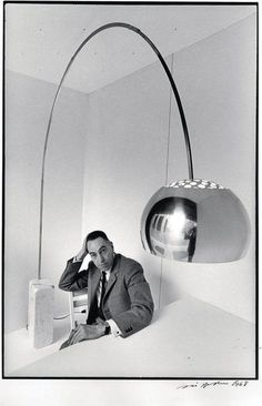Achille Castiglioni with his Arco Lamp This is how he designed the Arco Lamp to be used; In an office, coming from behind the seat to illuminate the table without bothering, not in a living room, as we usually see it!