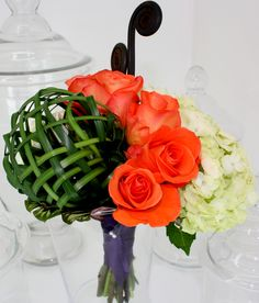This contemporary bridal bouquet features a weaved lily grass sphere, orange unique roses, hydrangea and a couple of fiddle heads.  Brenda Abbott Floral Design  www.brendaabbott.net  Brenda Abbott Floral Design  www.brendaabbott.netAbbott Floral Design  www.brendaabbott.netheads.