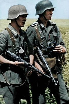 Members of the Wehrmacht armed with submachine guns MP38 and hand grenades Stielhandgranate M24 during the battle of Kerch city. Eastern Front, Crimea, 1942
