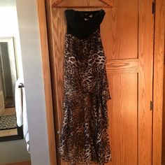 Leopard print strapless high low dress Rawr!! Love this animal print dress! Sexy material and built in slip and boob cups. Zipper concealed on the side. This is a gorgeous dress that requires more than an A-cup sized boon to pull off. Therefore I never wore it! It's brand new and ready for someone to be a party-animal in  I love the strappy cross cross back as well! Casting Dresses Strapless