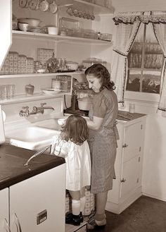 A woman doing dishes with her daughter, 1942 - no automatic dishwashers in those days!