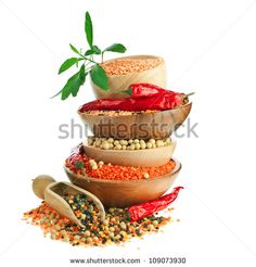Different colorful lentils in a wooden bowl, soya beans, red chilli peppers with leaves - stock photo