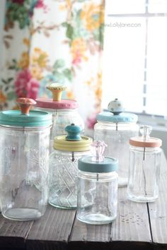 Add pretty knobs to the tops of mason jars for pretty mason jar storage solutions! Lots of options with this easy mason jar trick! Love these recycled food jars turned pretty storage jars with glass knob tops!