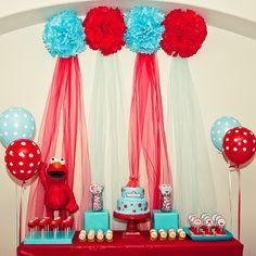 Pompones rojos y azules en la decoración mesa de postres tema Elmo.