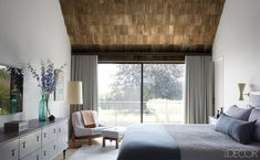 In the master bedroom, the bedding is by Matteo, the custom-made leather dresser is by BDDW, and the chair and ottoman by Sergio Rodrigues are upholstered in a BDDW fabric; the curtains are of a Maharam wool, and the ceiling is of weathered cedar shingles.