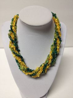 "Check my blog: centraltexascrafter.com or direct link below. Want the look of beads but enjoy the light-weight feel of yarn? Handcrafted, glittery and expandable beautiful green and gold necklace; perfect for your favorite Baylor Bear.  Length can be adjusted from 18"" to 24"" with ease. No metal, no clasps - easy to put on and wear. You'll get so many comments on your ""beads"" - this unique necklace will garner you many compliments!"