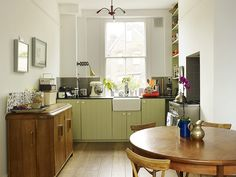 kitchen no upper cabinets apple green lower cabinets wood floor small efficient layout stove in alcove from Brixton house in The Guardian