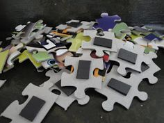 Glue magnetic strips on the back of puzzles. My little guy can put them together on the fridge or on a cookie tray.
