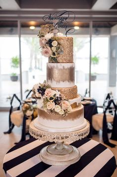 10 Winter Wedding Cakes That Creatively Ice Out Their Competition | A gold wedding cake with gilded details, sparkles and black and white floral decorations.