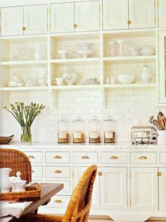 Traditional white kitchen cabinetry with brass hardware and white subway tile backsplash. Open shelving. Rattan wicker dining chairs.