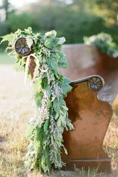 Organic Mountain Wedding draping greenery over church pew for wedding ceremony