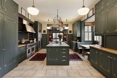 Dark green kitchen design with matching island. Love the concept but I would change the color scheme and extend the island or make it 2 islands.