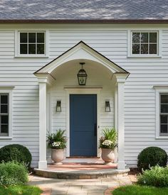 An oil rubbed bronze carriage lantern hangs from a portico in front of a blue front door flanked by oil rubbed bronze and glass sconces fixed to white siding. Front Porch Garden, Front Porch Planters, Front Porch Design, Garden Planters, Stone Planters, Exterior House Siding, Exterior Front Doors, Front Entry, Porch Over Front Door