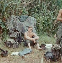 Jerry's RTO trying to cool his feet-west of Tam Ky, 1967. Note the lighweight rucksack on the left as well as the ERDL poncho liner laying on the brush. There also appears to be an M1 helmet in the left corner with no helmet cover.