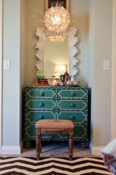 scalloped mirror, vintage french stool, turquoise chest of drawers, chevron rug, and a capiz chandelier.