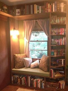 Cozy window seat surrounded by shelves. Love the details- lighting, cushions, corner cuts on the right side shelves...