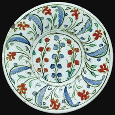 AN IZNIK POLYCHROME FLAT DISH, TURKEY, CIRCA 1585 of shallow rounded form, decorated in blue, red and green, the central section with three sprays of stylised budding flowers, the border with alternating saz leaves and hyacinths, the reverse with spiral and flower head motif