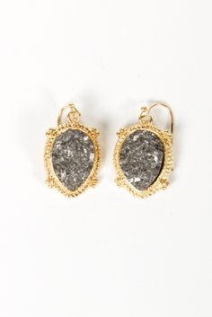 our framed druzy earrings feature a faux druzy stone in a graphite color, surrounded by an intricate golden frame
