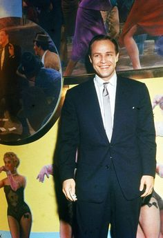 Marlon Brando smiling infront of a stage backdrop from Guys and Dolls, 1955.
