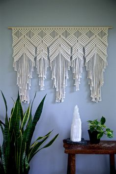 This extra large macrame wall hanging is made from 5mm natural white cotton rope and hangs from a wooden dowel. A unique piece that is sure to add texture and interest to any room! Would work especially well as a window valance or bedroom headboard! Would also make an amazing gift!  Wooden dowel is 48, macrame measures approx. 44 wide by 35 long.  You may choose for the wooden dowel to be stained a deep walnut color, or left natural as shown.  Please note: the exact piece in the photos has…