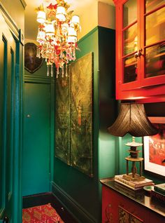 Emerald-green and coral paint give the entryway a moody feel.   Inspired by a Philip Treacy hat, they painted a brass chandelier (another junk-shop find) and adorned it with fake butterflies from the flower district.  The chinoiserie console was originally a fifties TV cabinet that they found in a junk shop on Atlantic Avenue in Brooklyn. -- New York Magazine