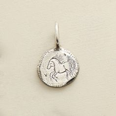 """STERLING SILVER COURAGE CHARM--A horse gallops across one side of Jes MaHarry's artisan sterling silver charm. """"Be brave"""" is inscribed on the other. Handmade in USA. 7/8""""W x 9/16""""L."""
