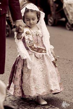 Valencian girl wearing the traditional dress (traje de fallera) going to the Ofrenda in Valencia, Spain (Fallas de Valencia)