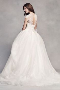 A romantic look with unique touches. An organic pick-up of textured organza adds an unexpected detail to the skirt of this classic ball gown. The illusion neckline and cap sleeves feature delicate lace appliques. White by Vera Wang, exclusively at David's Bridal Polyester Sash not Included Chapel train Back zipper; fully lined Dry clean Imported